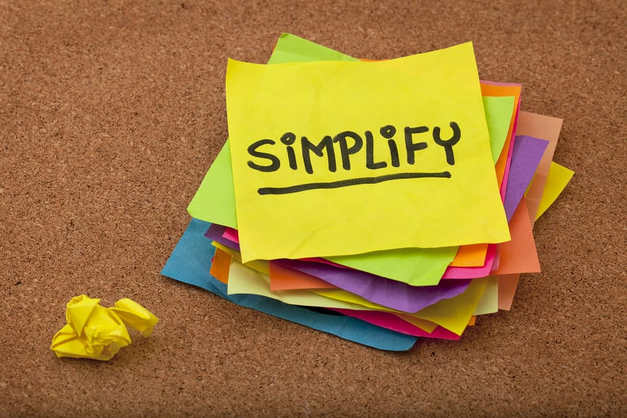 pragmatic or get organized concept, simplify reminder - a stack of colorful sticky notes on cork bulletin board