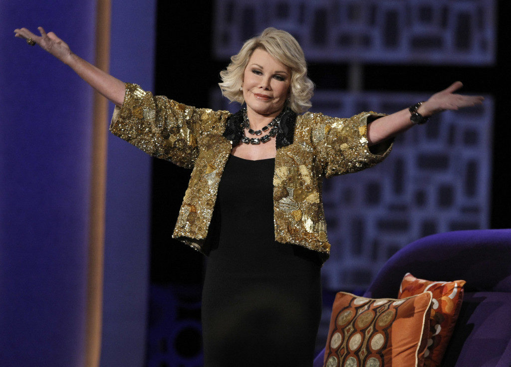 "FILE - In this Sunday, July 26, 2009 file photo, Joan Rivers greets the audience at the ""Comedy Central Roast of Joan Rivers"" in Los Angeles. Rivers, the raucous, acid-tongued comedian who crashed the male-dominated realm of late-night talk shows and turned Hollywood red carpets into danger zones for badly dressed celebrities, died Thursday, Sept. 4, 2014. She was 81. Rivers was hospitalized Aug. 28, after going into cardiac arrest at a doctor's office. (AP Photo/Dan Steinberg, File)"