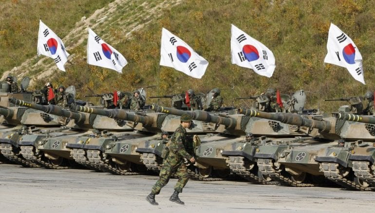 A South Korean army soldier runs in front of K-1 tanks after a live-fire military exercise as a part of the Seoul International Aerospace and Defense Exhibition 2011 on the Seungjin fire training field in Pocheon