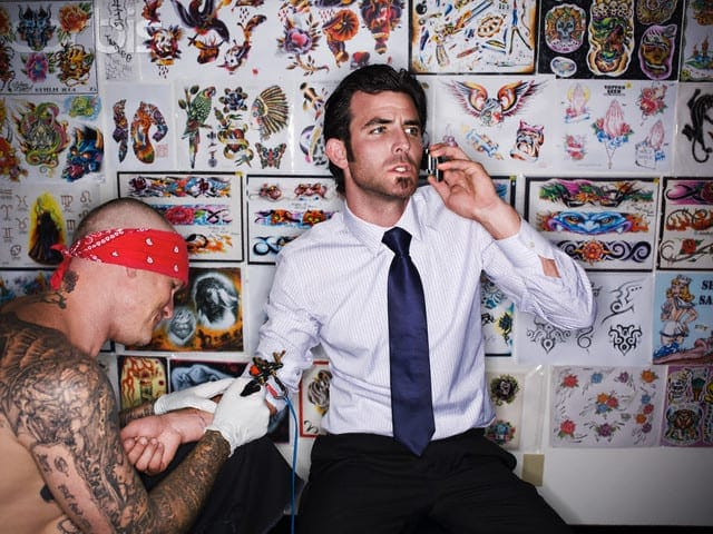 Businessman Talking on Phone While Getting Tattooed