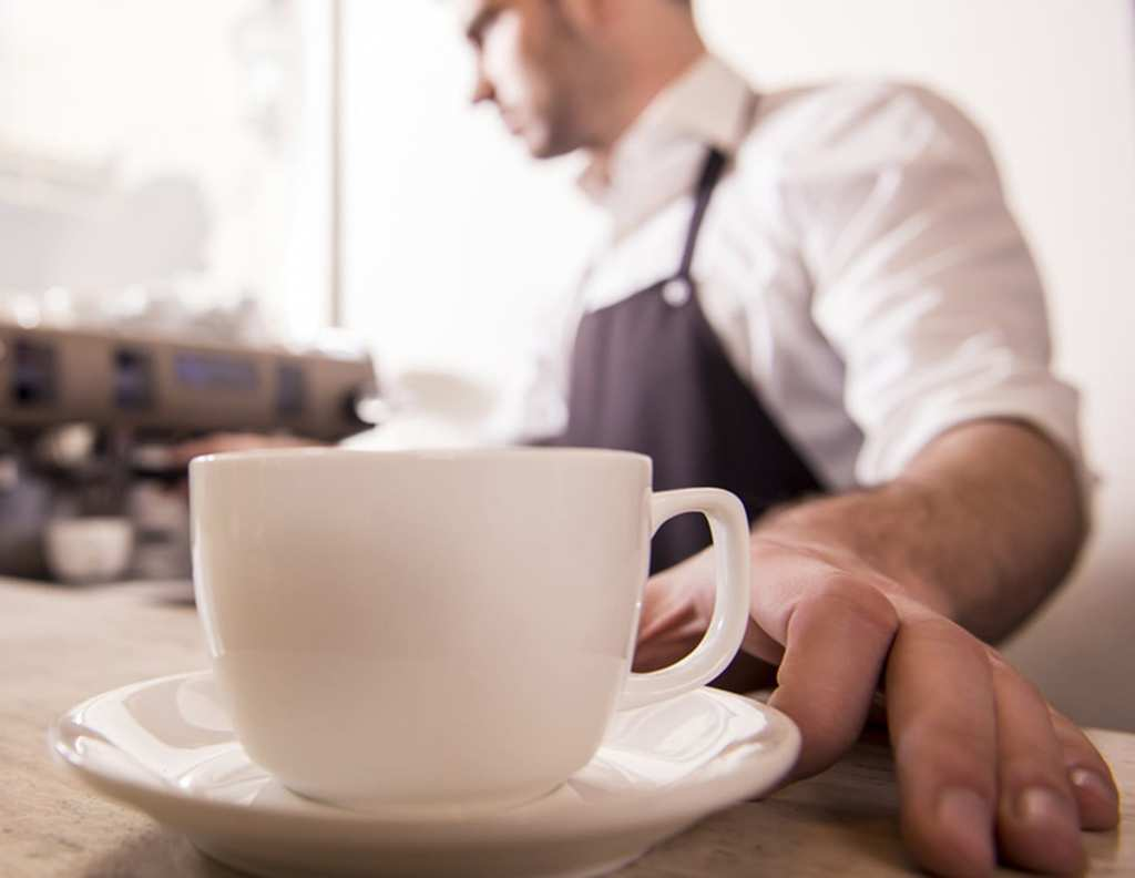 Man-Serving-Coffee-At-Restaurant