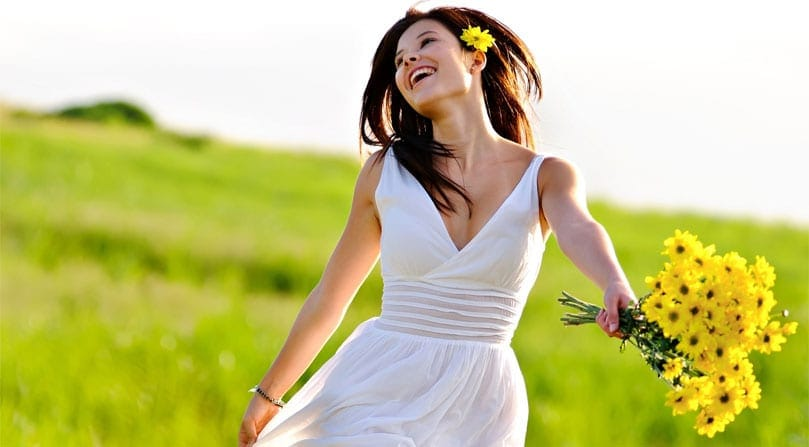 happy-woman-holding-flowers-in-the-field