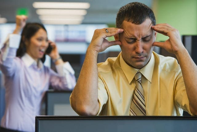 Businessman Irritated with Loud Coworker --- Image by © ColorBlind Images/Corbis