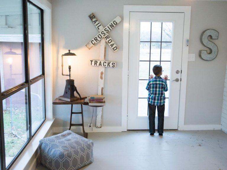 Five-year-old-Julian-Silva-peeks-into-the-driveway-from-the-new-side-door-of-the-family-room-as-seen-on-HGTVs-Fixer-Upper.-Chip-and-Joanna-Gaines-rebuilt-the-crumbling-wall-and-door.-768x576