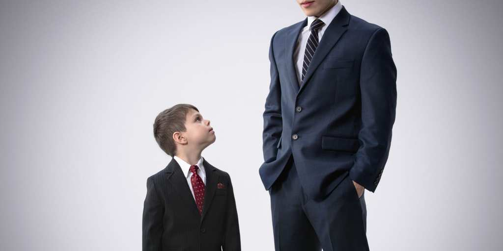 Boy in suit looking at businessman father